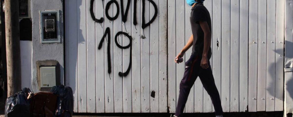 """Un hombre con barbijo caminando por la vía pública. De fondo se lee """"Covid 19"""" pintado con aerosol sobre un portón."""